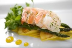 Shrimp with asparagus atop yellow tomato aioli