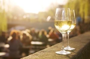 Two glasses of chardonnais on a sunlit cafe terrace.