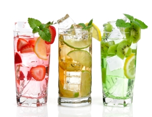 Glasses Of Drink With Ice Cubes And Fruits On White Background